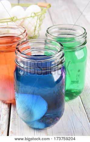 Dyeing Easter eggs in mason style jars, Three jars with different dyes and egg carton and basket in the background.