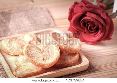 Paddle a butterfly heart shaped patty crispy with sugar in a wooden plate The concept of Valentine's Day.