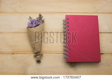 top view bouquet flower and red cover notebook put on wooden floor background