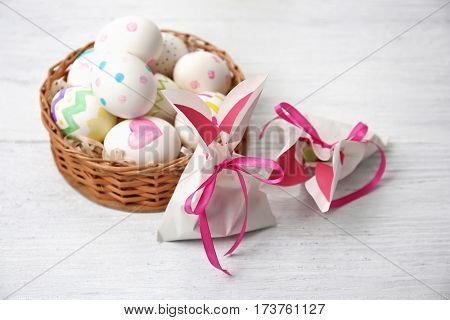 Paper bags in shape of Easter rabbits and wicker basket with painted eggs on wooden table