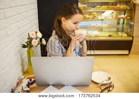 Young girl sitting at table in cafeteria and drinking coffee. Shopwindow with cakes on background. Open laptop on desk. Female dressed in striped shirt and jeans. Mysterious romantic person