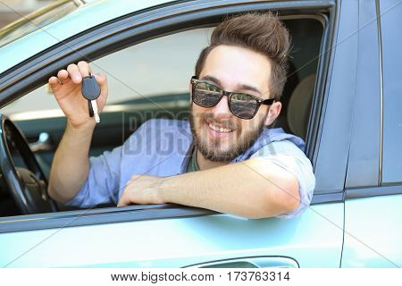 Successful young driver showing car key through open window