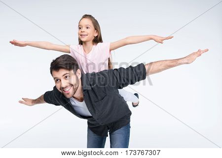 Happy father piggybacking little daughter with open arms on white