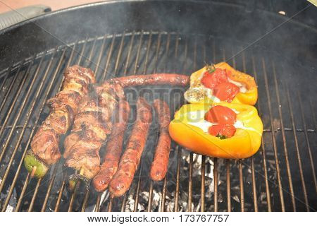 Delicious french sausages and meat on the barbecue grill
