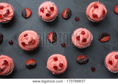 Chocolate-dipped strawberry slices and cupcakes with pink frosting topped with candy hearts for backgrounds