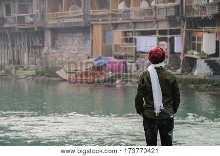 Guy young man alone with a travel backpack in Fenghuang Ancient town background. Fenghuang Ancient Town at after rainy day. Located in Fenghuang County. Southwest of HuNan Province China.