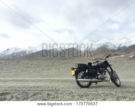 Motorcycle alone enduro traveler with suitcases standing on rocky plateau in cloudy weather on the background of endless mountain steppe Plateau Ukok Altai mountains Siberia Russia.