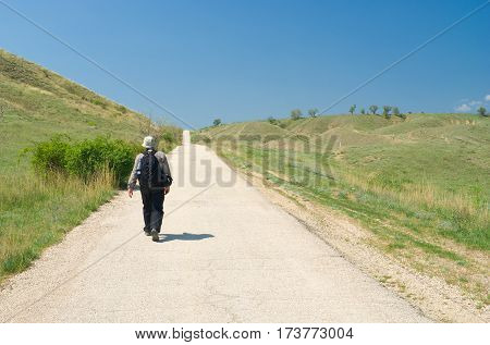 Lonely tourist on Crimean road at early spring season.