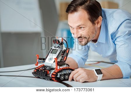 Like what you do. Pleasant cheerful smiling engineer holding robot and making an experiment while being involved in work
