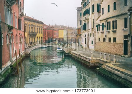 Foggy (misty) Venice. Canal (channel), historical, old houses and boats in thick fog. Scenic cityscape view. Venice, Italy