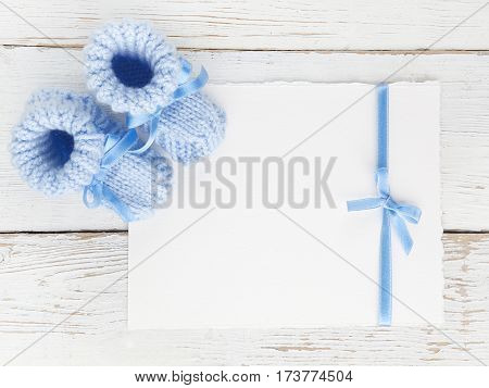 Baby boy booties with a blank card on a white wooden background. Top view
