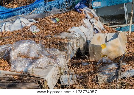 Garbage and trash left on an old wooden table covered in a white vinyl tarp and dry dead twigs