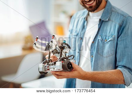 Great device. Close up of robot in hands of positive engineer holding it and expressing gladness while standing in a lab