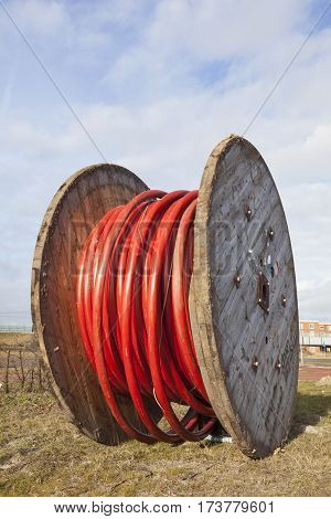 large wooden spool with heavy red underground cable