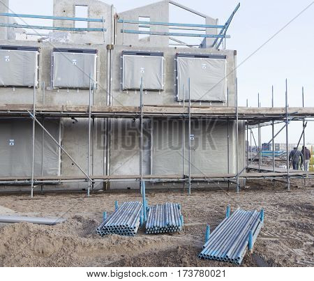 concrete frame of newly built house with scaffolding around and metal pipes
