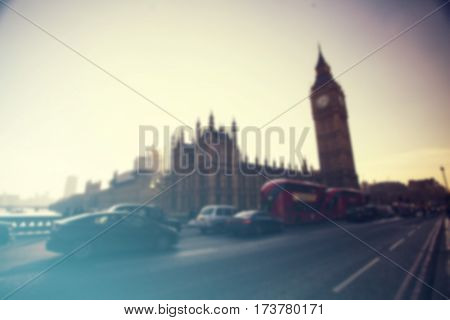 Defocused background of London traffic near Big Ben of Westminster in rush hour with famous red busses.