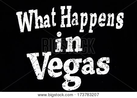 What Happens in Vegas. White ink brush lettering isolated on black background. Lucky saying for cards, posters and t-shirt