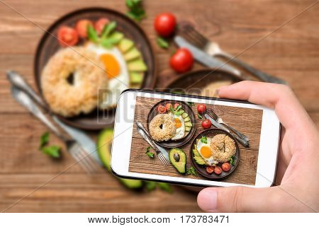 Hands taking photo bagel with avocado and egg with smartphone.