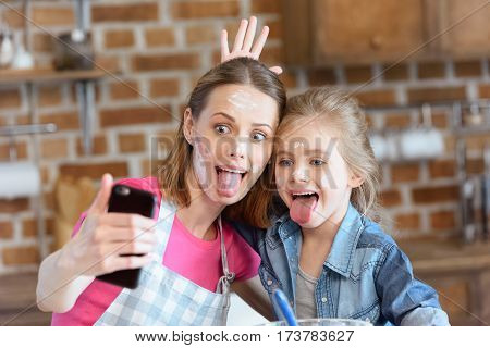 portrait of grimace mother and daughter making selfie while cooking at home