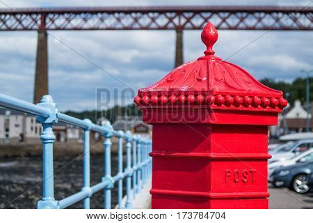 Red letterbox and Firth of Forth rail bridge in Edinburgh, Scotland UK