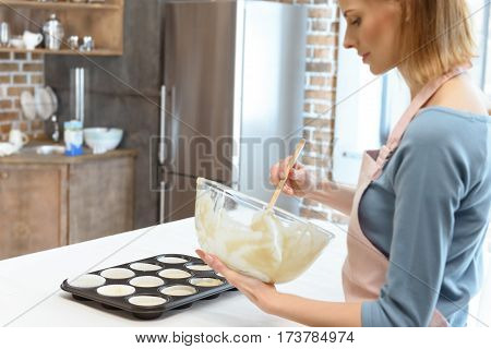 Smiling young woman in apron mixing dough in glass bowl
