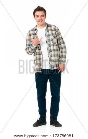 Happy young student boy showing rock-n-roll sign, isolated on white background