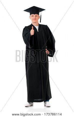 Handsome graduate guy student in mantle showing thumb sign, isolated on white background