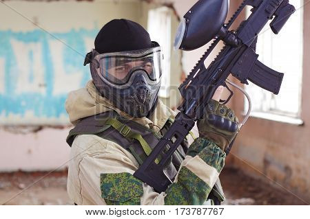 Shot of militaty man in mask with paintballing weapon