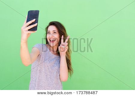 Happy Young Woman Taking Selfie With Hand Peace Sign