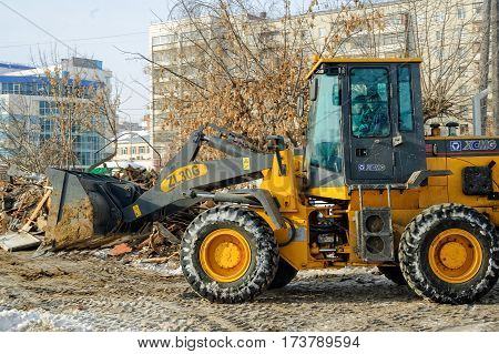 Tyumen Russia - February 16 2008: Bulldozer removes debris from demolition of old derelict buildings between Profsoyuznaya and Severnaya streets