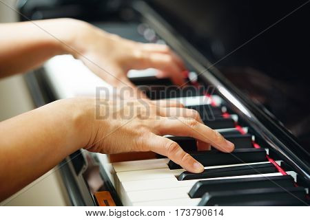 Scene of pianist hands from beside angle playing piano. Selective focused.