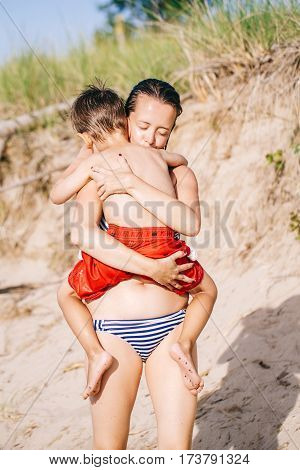 Group portrait of white Caucasian mother and son child boy playing hugging on sand beach near sea ocean lake healthy active emotional lifestyle.