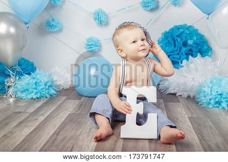Portrait of cute adorable Caucasian baby boy with blue eyes barefoot in pants with suspenders and hat sitting on wooden floor in studio holding large letter E looking away first year concept