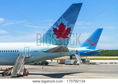 CANCUN, MEXICO - JULY 10, 2011: Airplanes on the runway of Cancun International Airport in Mexico. Airport is lacated on the Caribbean coast of Yucatan Peninsula, its second busiest airport in Mexico.