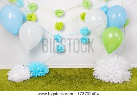 Festive background decoration for first birthday celebration or easter holiday with blue green and white paper flowers balloons fluffy rug on floor with nobody copyspace for text