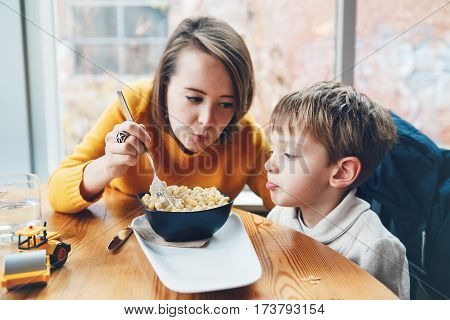 Portrait of white Caucasian happy family mother and son sitting in restaurant cafe at table feeding eating pasta spaghetti authentic lifestyle