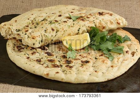 Fresh garlic and coriander naan garnished with lemon and coriander leaves