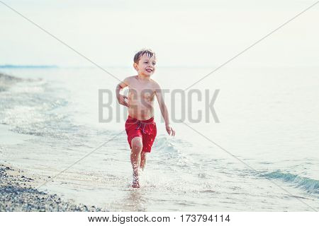 Portrait of funny adorable white Caucasian one young little boy in red swim shorts running on beach by water ocean sea emotional healthy active lifestyle summer