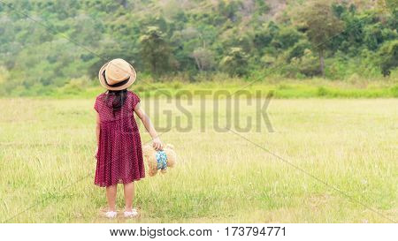The Back Of A Girl Holding A Doll Standing In The Garden.