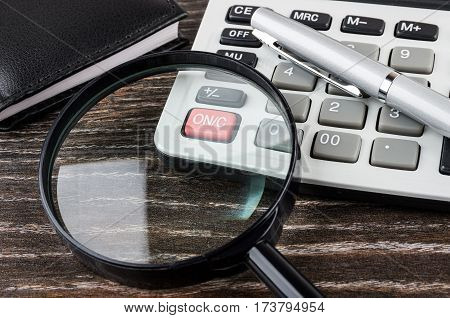 Close Up Of Electronic Calculator, Notepad, Magnifying Glass And Pen