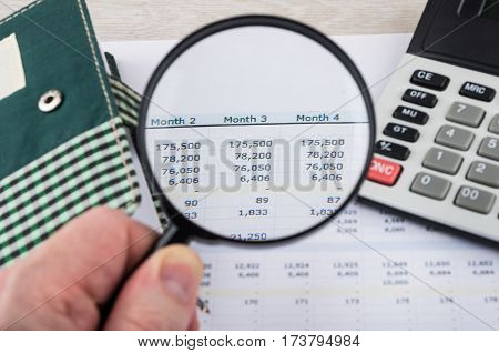 Looking Numbers On Printout With Magnifying Glass