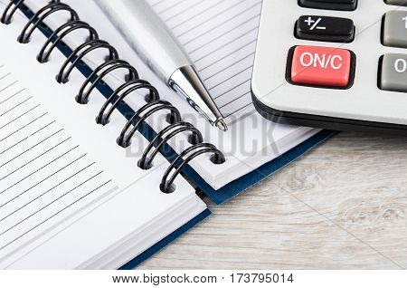 Close up of open notepad ballpoint pen and electronic calculator on wooden table