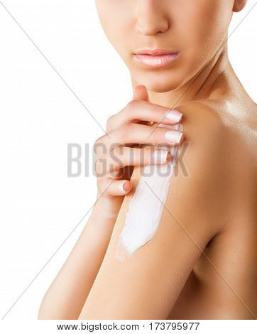 Close-up of a woman taking care of her forearm applying cosmetic cream. Isolated on white background