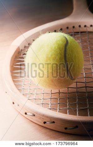 Retro tennis shot. A fluffy yellow ball resting on the strings of an old wooden racquet circa 1970s.