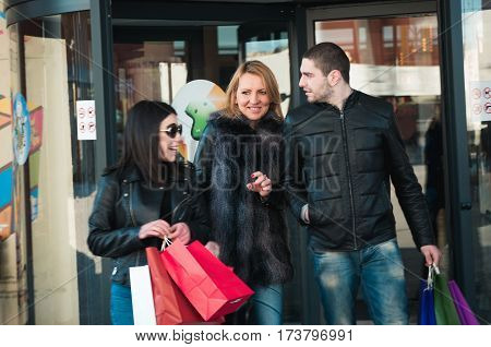 Happy friends making shopping in the shopping center