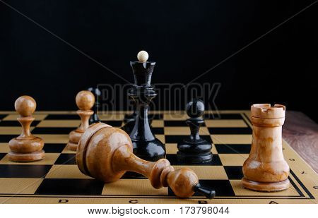 The chess pieces are placed on the chessboard. Defeated white king. Dark background