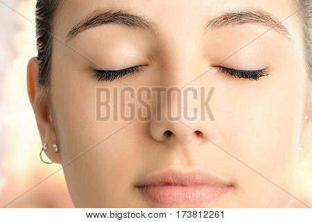 Extreme close up face shot of attractive young woman meditating with eyes closed against colorful bright background.