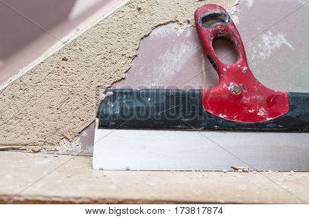 Repairing fireplace surface with spackle and trowel by hand