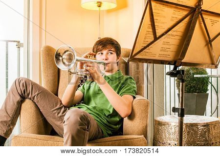 Photo of a teenage male practicing his trumpet at home.