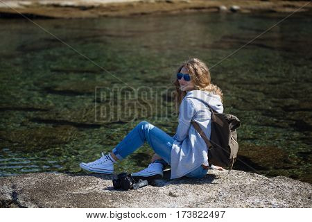 Blond woman tourist wearing sunglasses khaki backpack gray jacket and jeans sitting and relaxing on shore with blurred water background
